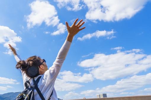 女性 万歳 空に向かって万歳 喜んでる