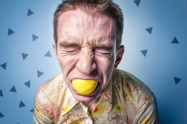 レモンをかじっている男性の顔