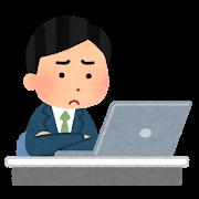 パソコンの前に腕組する男性