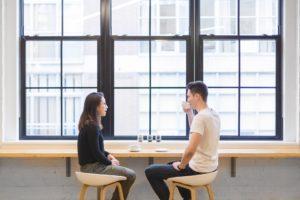 喫茶店 男女が窓側の席でお茶を飲む