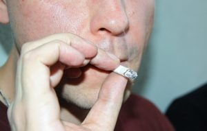 くわえタバコする男 根本までしつこく吸っている