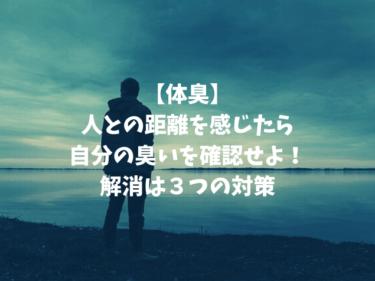 暗い海辺をびんやり見ている男性の写真