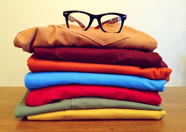 服を縦に積んでおいてある 上に眼鏡が置いてある