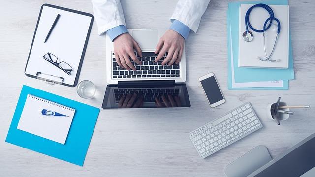 医師がパソコン作業 聴診器 眼鏡 ボールペン 白衣