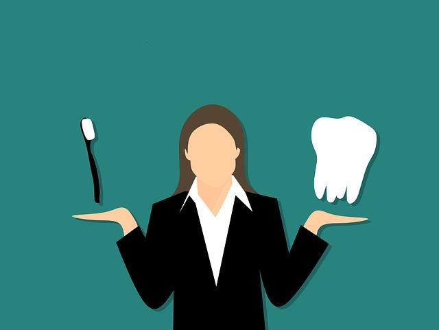 女性が 右手に歯ブラシ 左手に歯の模型 を持つ