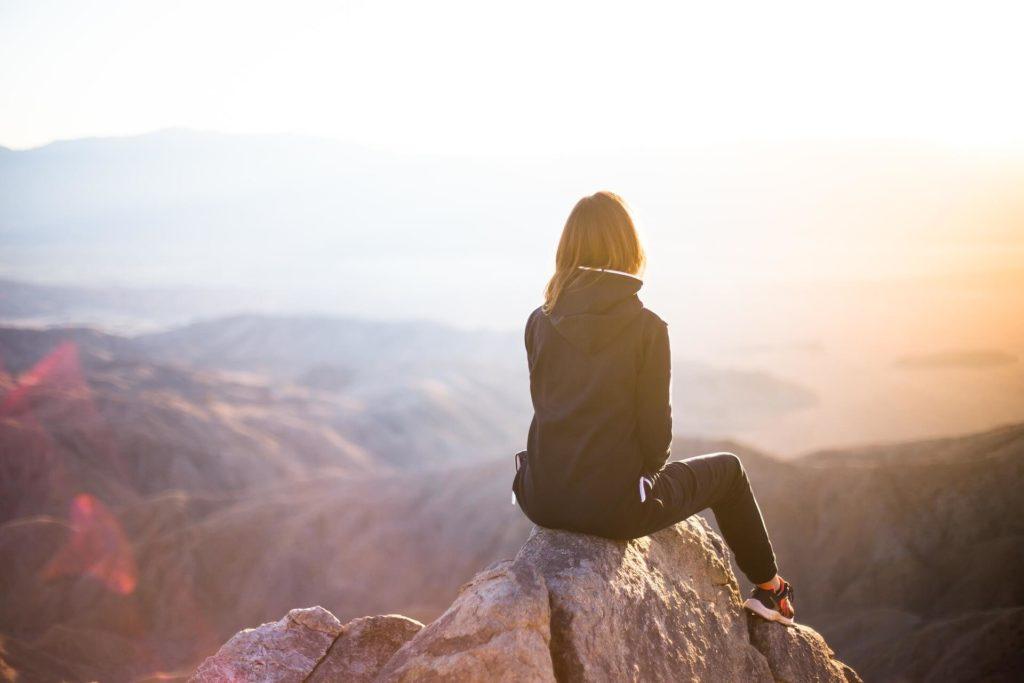 女性が山の頂上で座っている