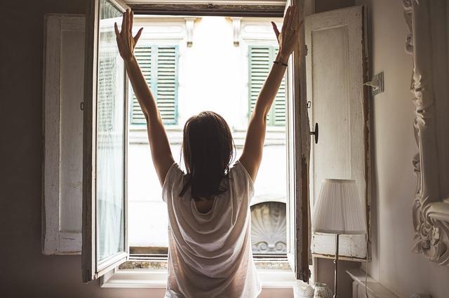 窓を開けて外に向かって大きく手を広げる女性
