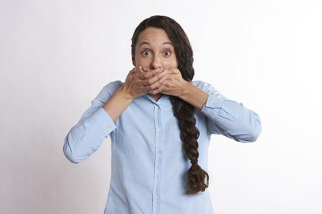 口をふさぐ女性