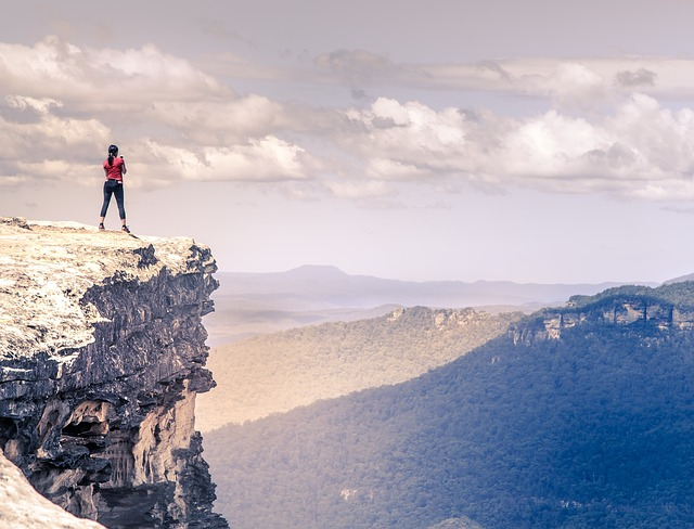 女性が山の頂上から景色を見ている
