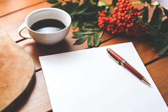 コーヒーと紙とペンの写真