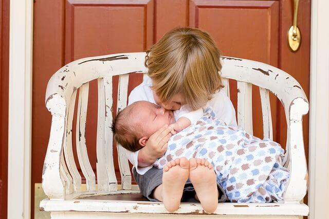 幼児が赤ちゃんを抱っこしている写真