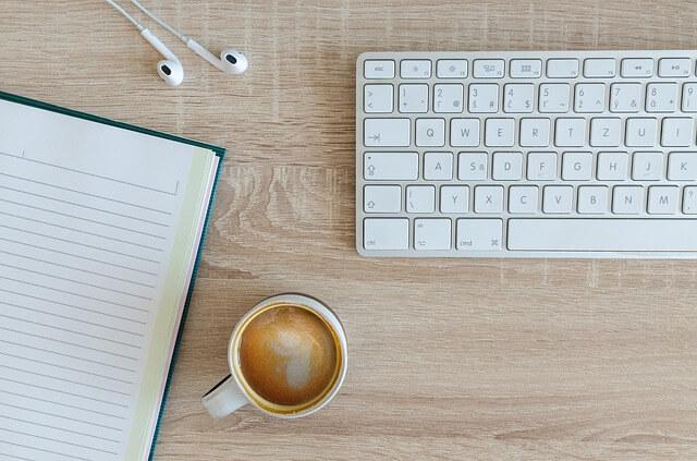パソコンのキーボード ノート コーヒーの写真