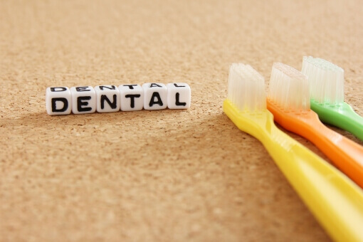 dentalと書いたブロック 歯ブラシが3本置いてある