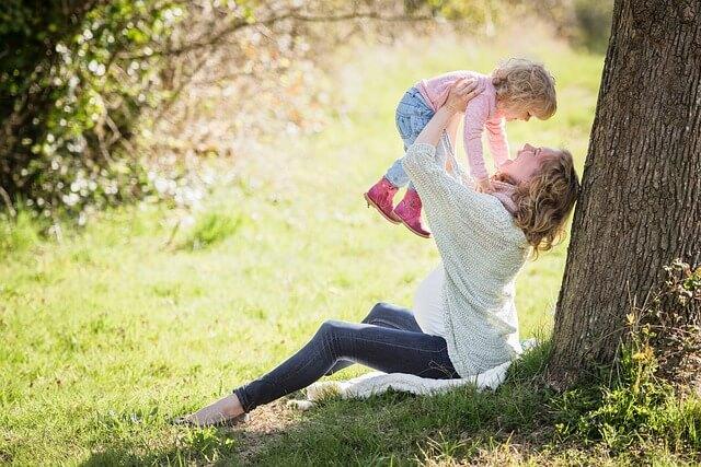お母さんが子供を抱き上げて笑っている写真