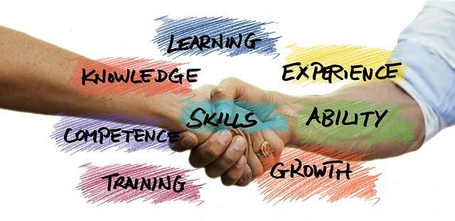 二人が握手している写真 文字は learning  knowledge  skills  ability  competenc  growth などが書いてある