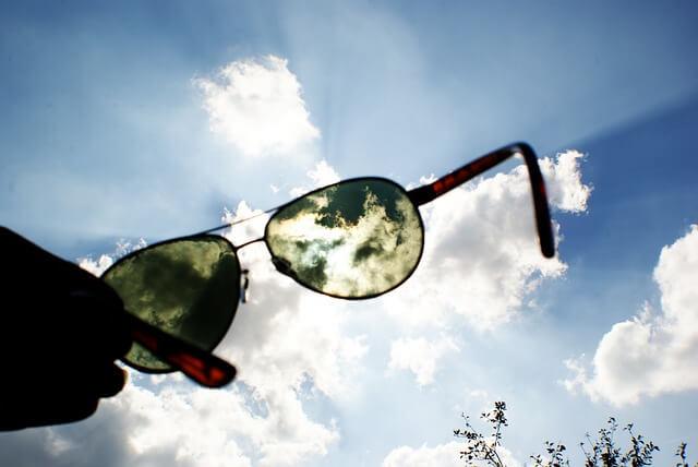 サングラスを持って空を見ている写真