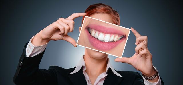 キレイな歯の写真を持った女性