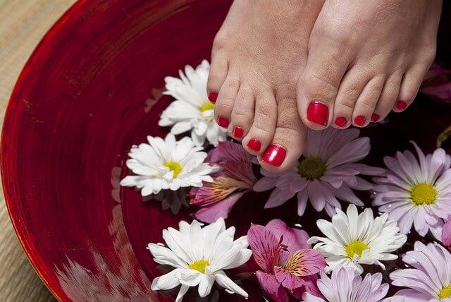 ペディキュアを塗った女性の足が花びらの上に見えている