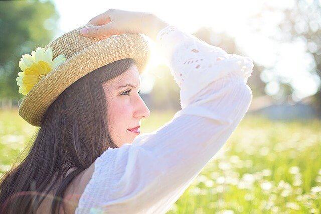 花畑で帽子をかぶり笑顔の女性の横顔の写真