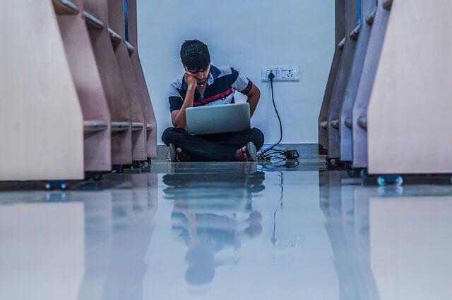床に座ってパソコンを見る男性